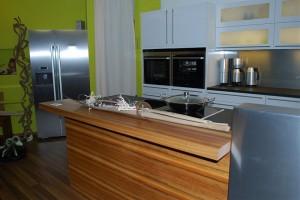 Offene Musterküche in Hochglanz Weiß, Kücheninsel mit senkrechter Holzmaserung und Küchengeräten