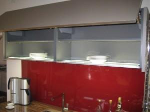 Küchenzeile einer Musterküche mit weißen Fronten, grauen Hängeschränken und roter Nischenrückwand